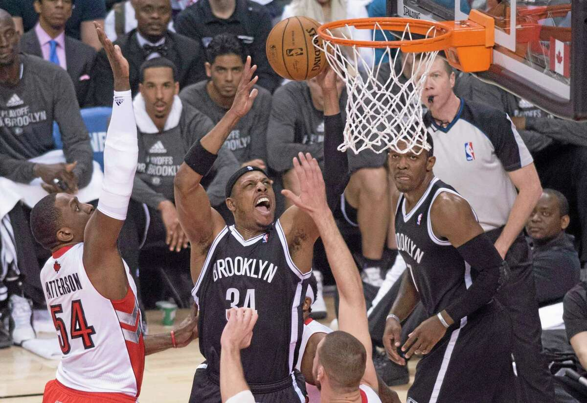 The Brooklyn Nets' Paul Pierce, center, drives to the net against the Raptors' Patrick Patterson, left, during the first half of Game 1 of an opening-round playoff series in Toronto on Saturday.