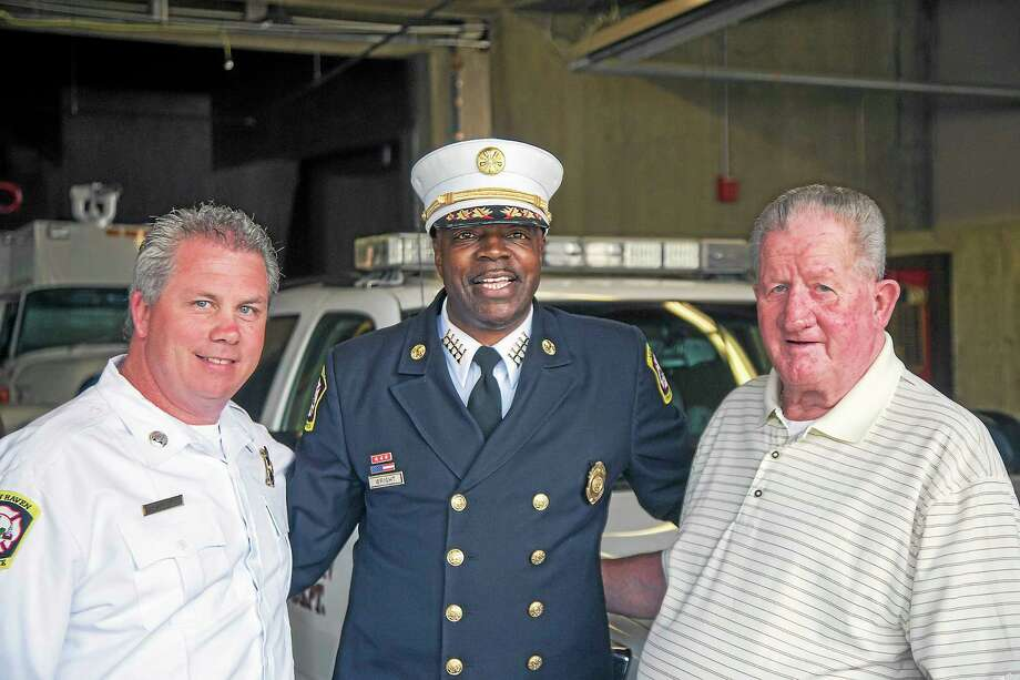 Newly promoted Battalion Chief Billy Gould, left, stands with Chief Allyn Wright, center, and his father, retired Batallion Chief Thomas Gould. Photo: Rich Scinto/New Haven Register