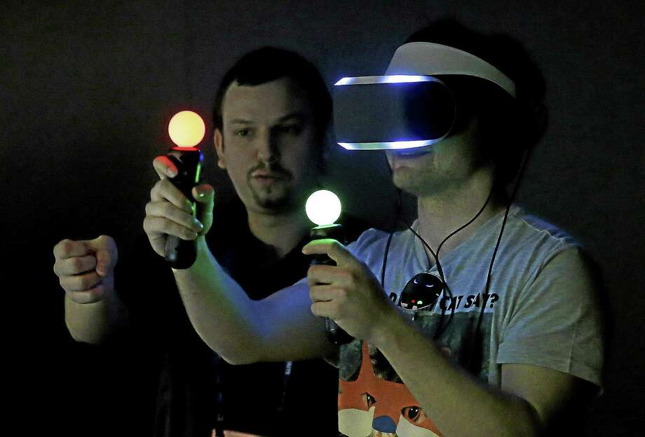 In this March 19, 2014 photo, Marcus Ingvarsson, right, tests out the PlayStation 4 virtual reality headset Project Morpheus in a demo area at the Game Developers Conference 2014 in San Francisco. Photo: AP Photo/Jeff Chiu, File   / AP