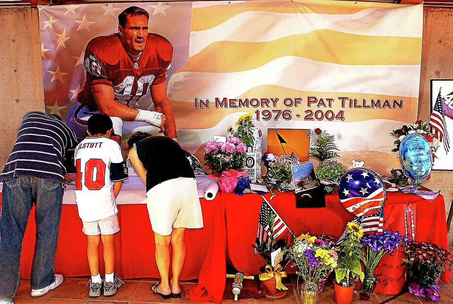 Fans sign a memorial for former Arizona Cardinal and U.S. Army Ranger Pat Tillman on April 23, 2004 at the Cardinals training facility in Tempe, Ariz. The 10-year anniversary of Tillman's death is this week. ESPN will air an episode of Outside the Lines on Sunday morning in which a fellow Ranger says he may be the one who fired the fatal shots. Photo: Matt York — The Associated Press File Photo   / 2004 AP