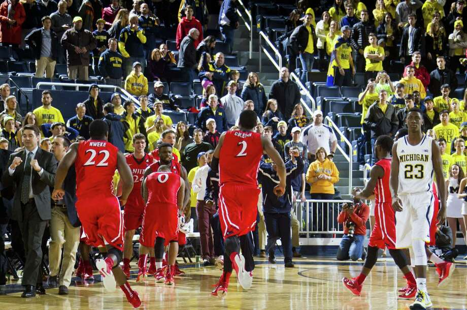 NJIT head coach Jim Engles, far left, celebrates with his players as Michigan guard Caris LeVert (23) walks off the court after Saturday's game at Crisler Center in Ann Arbor, Mich. Photo: Tony Ding — The Associated Press   / FR143848 AP