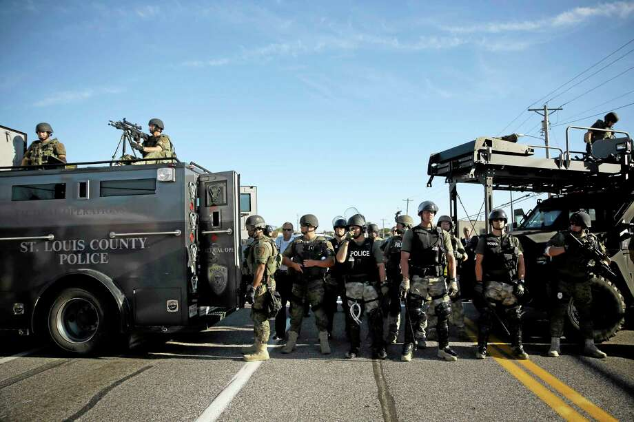 Police in riot gear watch protesters in Ferguson, Mo. on Wednesday, Aug. 13, 2014. On Saturday, Aug. 9, 2014, a white police officer fatally shot Michael Brown, an unarmed black teenager, in the St. Louis suburb. (AP Photo/Jeff Roberson) Photo: AP / AP