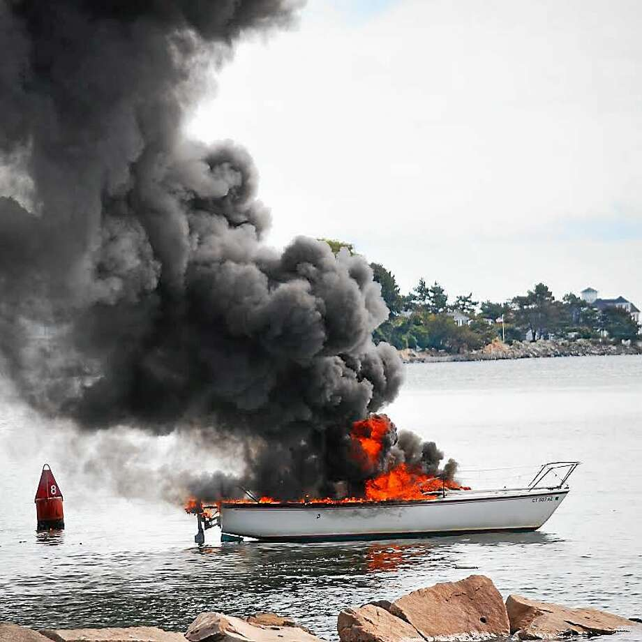 A sailboat caught fire in Milford harbor Friday at about noon. The lone occupant of the boat suffered superficial burns to his face. Photo: Contributed Photo — Michael Kauffman
