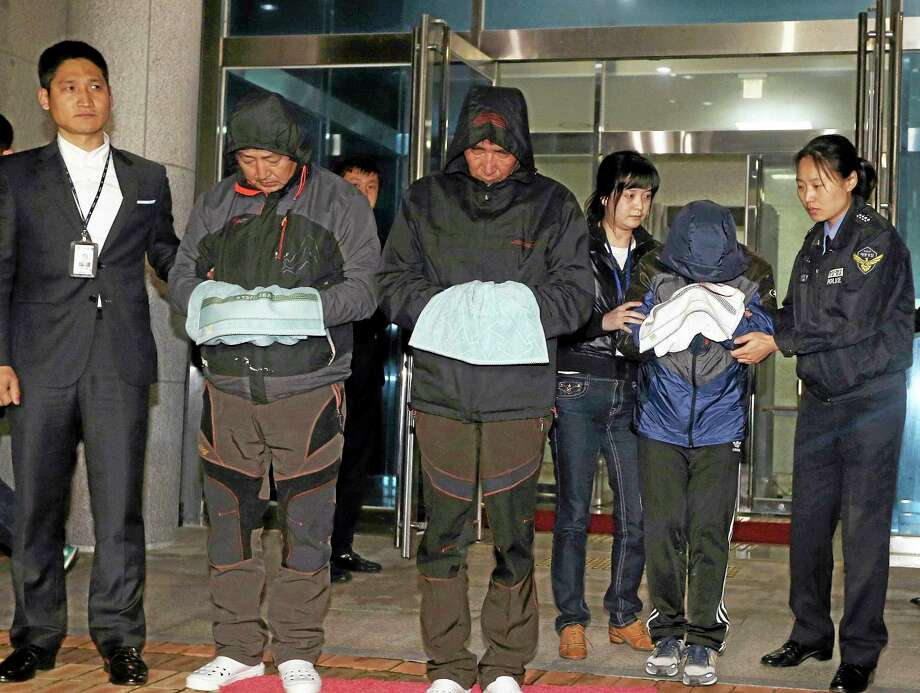 Lee Joon-seok, third from left, the captain of the ferry Sewol that sank off South Korea, and two crew members prepare to leave a court, which issued their arrest warrant Saturday. The captain of the sunken ferry, leaving more than 300 missing or dead, was arrested early Saturday on suspicion of negligence and abandoning people in need. Two crew members also were taken into custody, including a mate who a prosecutor said was steering in challenging waters unfamiliar to her when the accident occurred. Photo: Associated Press   / Yonhap