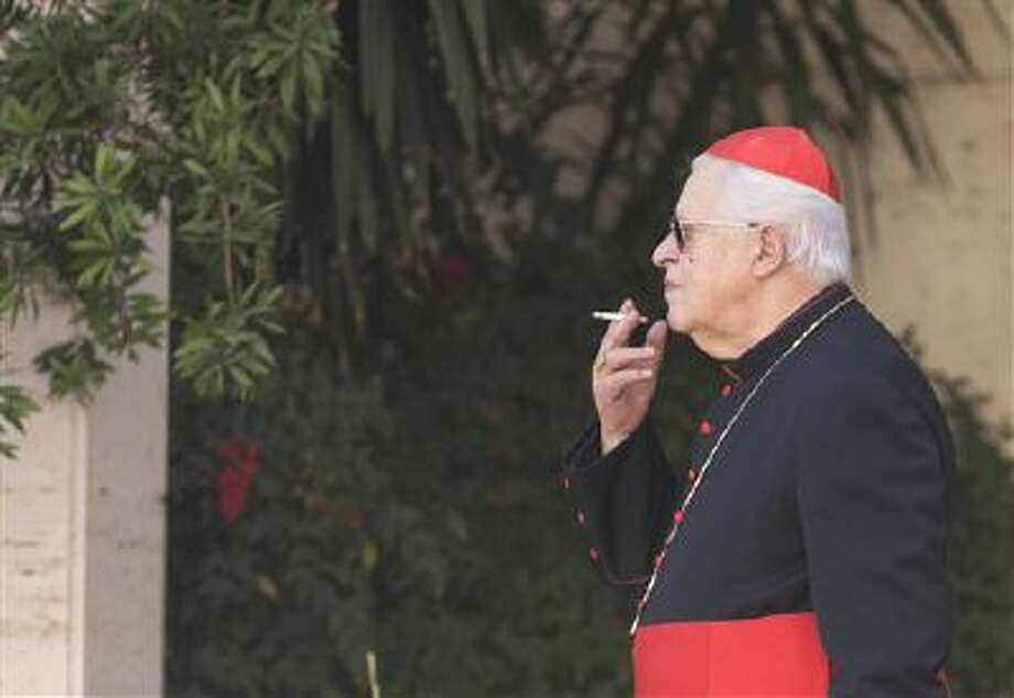 """Cardinal Jose' Policarpo  smokes during a pause of the morning session of an extraordinary consistory in the Synod hall at the Vatican City, Friday, Feb. 21, 2014. Pope Francis is leading a two-day meeting urging his cardinals to find """"intelligent, courageous"""" ways to help families under threat today without delving into case-by-case options to get around Catholic doctrine. He said the church must find ways to help families with pastoral care that is """"full of love.""""(AP Photo/Alessandra Tarantino) Photo: AP / AP"""
