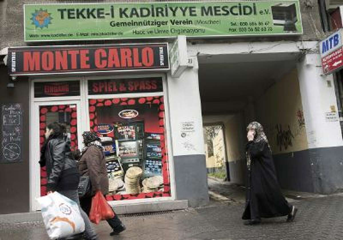 BERLIN, GERMANY - NOVEMBER 02: Muslim women pass a casino at Karl-Marx-Strasse in Neukoelln district on November 02, 2013 in Berlin, Germany. According to recently published statistics, 7.2 million foreigners were living in Germany by the end of 2012, which is the highest number ever recorded. Of those 80% are from countries in the European Union, while the rest come primarily from Turkey, Russia, the former Soviet states and Arab countries. (Photo by Carsten Koall/Getty Images)