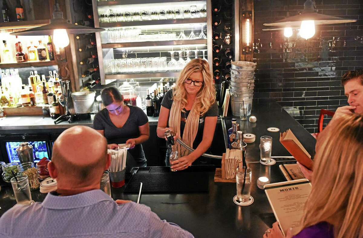 Helen Blanchard, far right, and bartender Jaimee Blanchard, serve customers at the new Moxie Restaurant on Wall Street in Madison during a soft opening Tuesday evening.