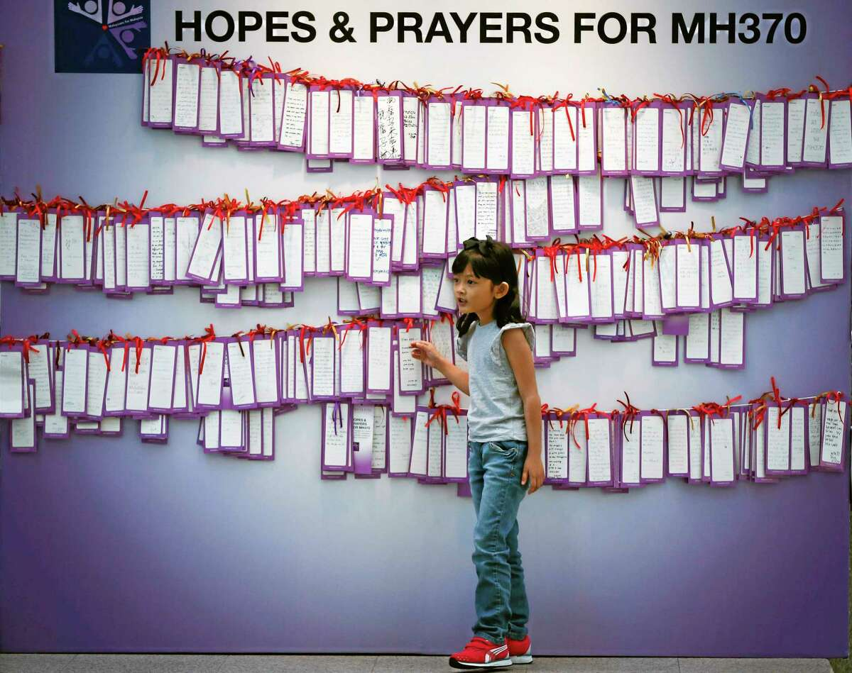 A girl stands in front of message cards for passengers onboard the missing Malaysia Airlines Flight 370 at a shopping mall in Kuala Lumpur, Malaysia on April 11.