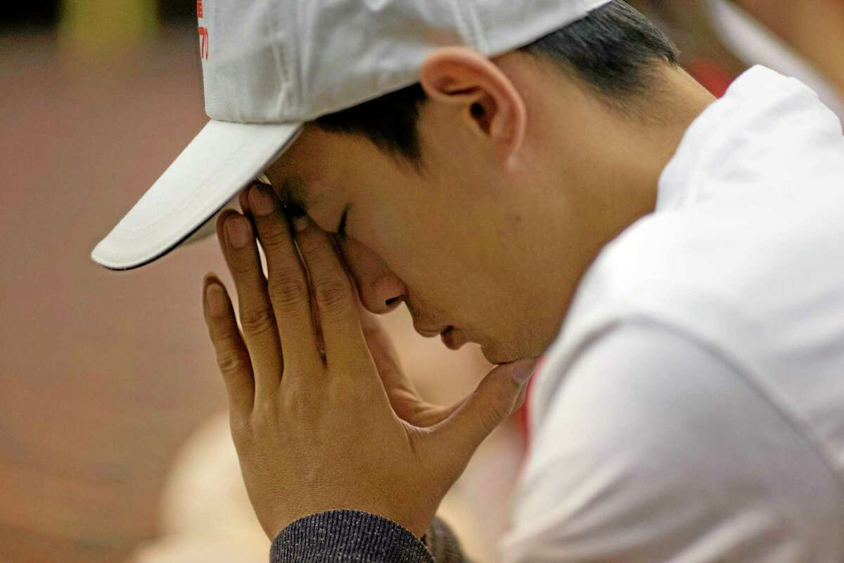 One of relatives of Chinese passengers on board the Malaysia Airlines Flight 370 pray at a hotel conference room Friday in Beijing, China. A robotic submarine headed back down into the depths of the Indian Ocean on Friday to scour the seafloor for any trace of the missing Malaysian jet one month after the search began off Australia's west coast, as data from the sub's previous missions turned up no evidence of the plane.