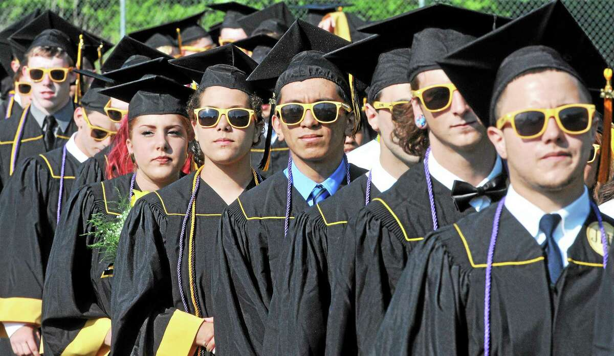 Jonathan Law High School seniors head to the football field for graduation ceremonies Tuesday in Milford.