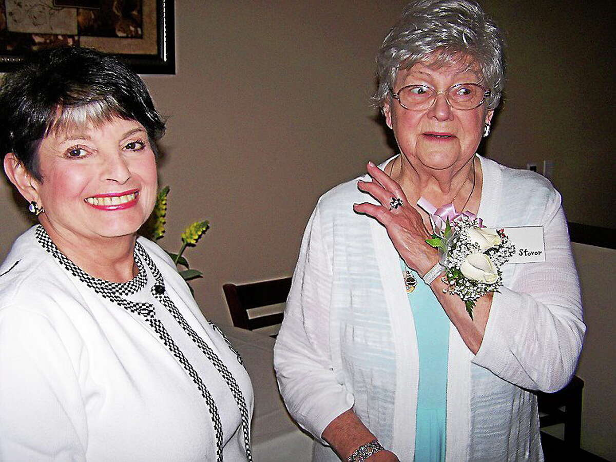 Founding member Lois Stover shows her wrist corsage to Lynda O'Donnel at the 60th anniversary celebration of North Haven Garden Club recently at Bellini's restaurant. Stover's husband, Stuart Stover; son, Dwight Stover; and daughter, Caroline Cody with her husband, Elden Cody, were special guests. Scholarships were awarded to Brianna Brockett, who will be attending the University of Vermont, and Gabrielle Longobardi, who will be attending the University of Hartford. First Selectman Michael J. Freda, Federated Garden Clubs of Connecticut President Jacqueline Connell, and past members of the Junior Garden Club also attended.