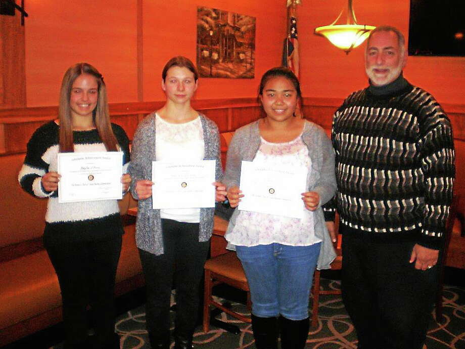 In this file photo, East Haven High School students Kaylee O'Brien, Natalia Wiszniewski and Donita Canieso join East Haven Rotary President Robert Parente. Each student was honored as 'Student of the Month' during the first three months of the school year. They were invited to dinner and were awarded $100 for their achievements. Contributed photo Photo: Journal Register Co.