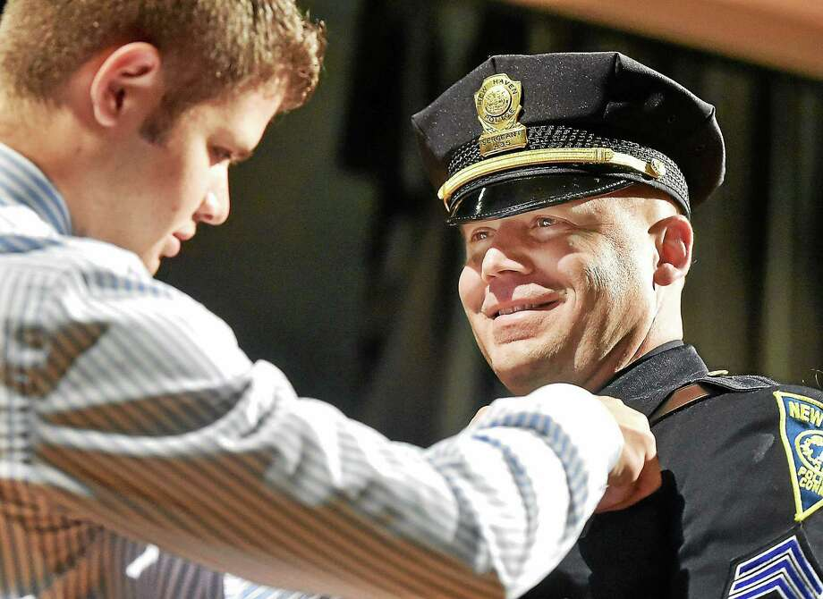 (Catherine Avalone - New Haven Register)   Matthew Merced pins a sergeants badge on his father, Det. Alberto Merced during a promotion ceremony held by the New Haven Department of Police Service ,  Friday, December 5, 2014 at Hill Regional Career High School at 140 Legion Ave. in New Haven. In total, 25 men and women in the department were promoted, five captains, four lieutenants and 16 sergeants including Merced. Photo: Journal Register Co. / New Haven RegisterThe Middletown Press