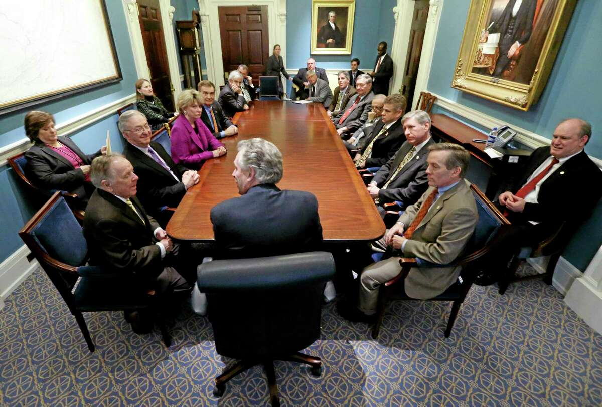 Gov. Terry McAuliffe, center, confers with the members of the Senate Finance committee, left, and House Appropriations committee, right, who are conferees on the budget bill, in the governor's conference room at the state Capitol Wednesday in Richmond, Va.