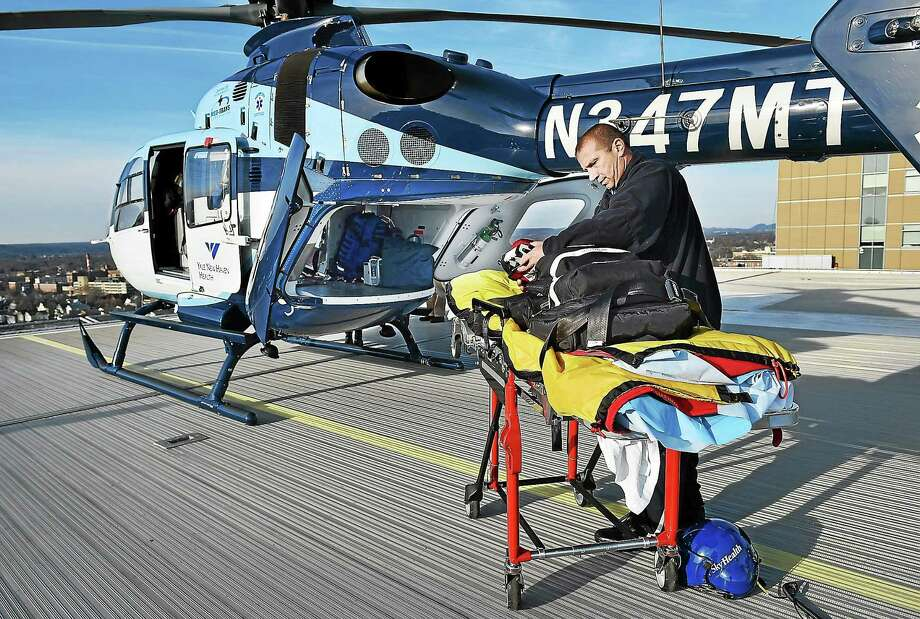 Paramedic Shawn Bowe gets ready to load the stretcher into SkyHealth on Thursday, December 4, 2014 at Yale-New Haven Hospital. Photo: (Catherine Avalone — New Haven Register)    / New Haven RegisterThe Middletown Press