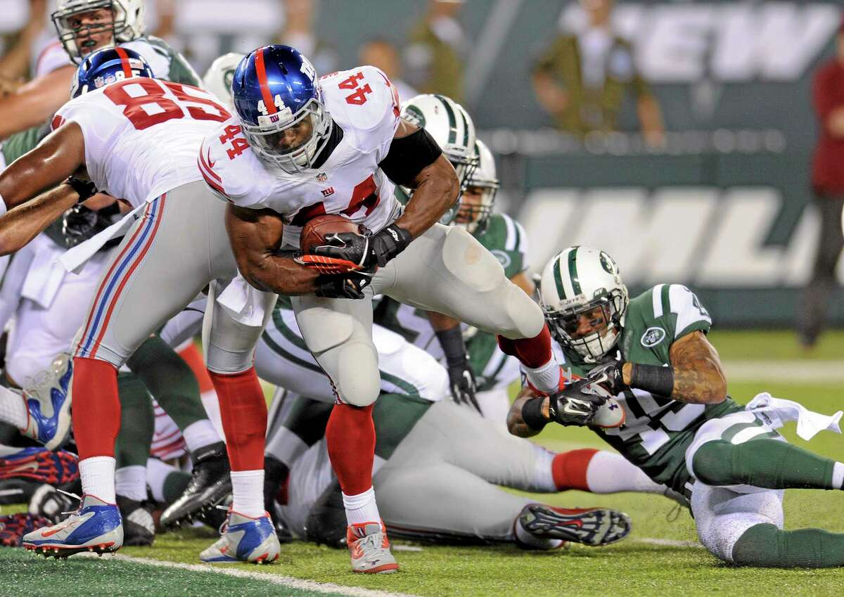 New York Giants running back Andre Williams (44) slips away from New York Jets defensive back Rontez Miles (45) to score a touchdown during a Aug. 22 preseason game in East Rutherford, N.J.