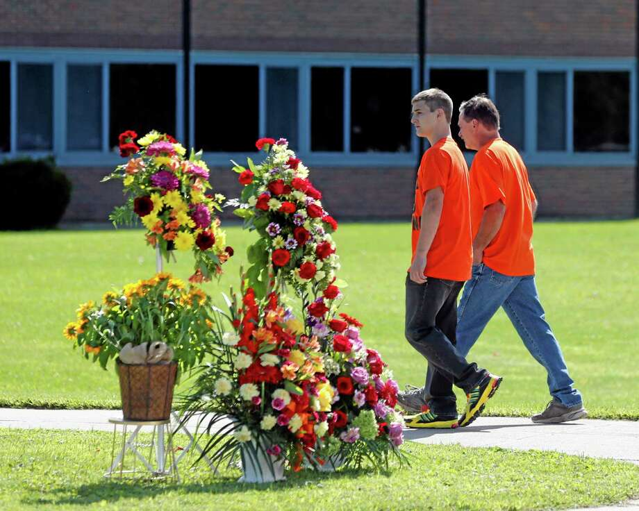People walk to South Lewis Central School before a funeral for race car driver Kevin Ward Jr., on Thursday, Aug. 14, 2014, in Turin, N.Y. Ward died after being struck by NASCAR driver Tony Stewart's car during a race last weekend at a dirt track in western New York. (AP Photo/Mike Groll) Photo: AP / AP