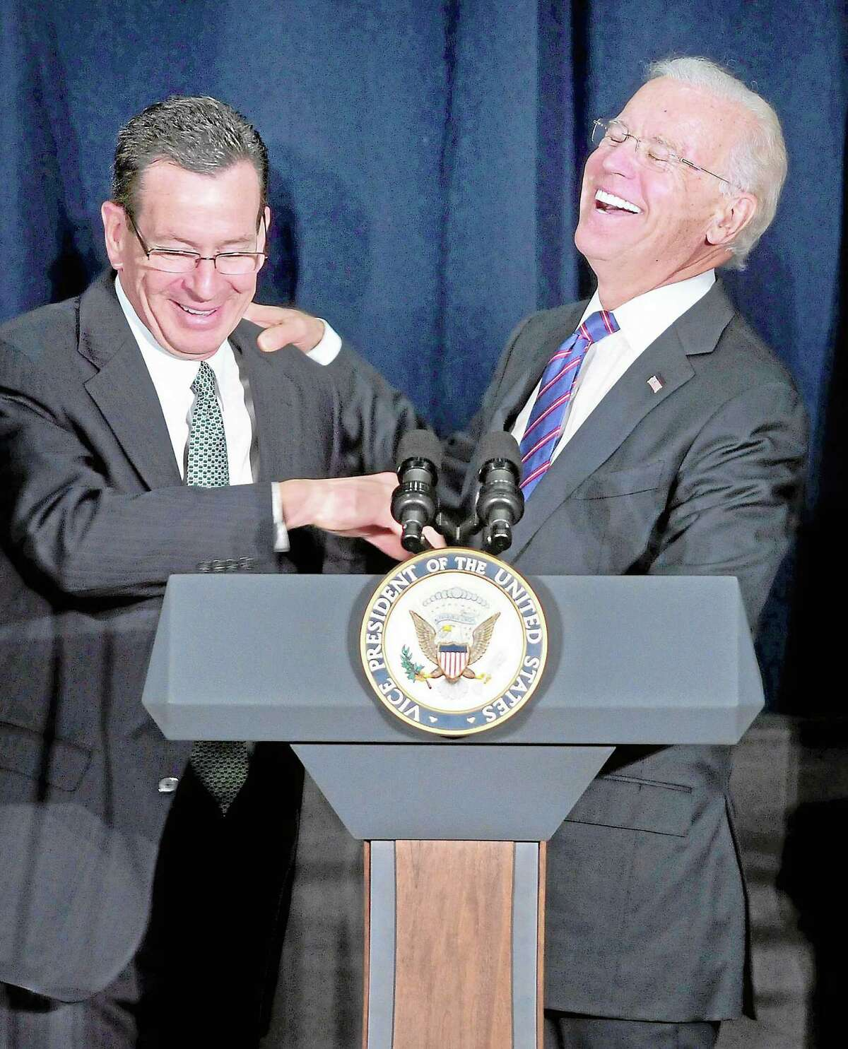 Gov. Dannel Malloy (left) jokes with Vice President Joe Biden (right) as he begins to speak at a Conference on Gun Violence at the Campus Center Ballroom at Western Connecticut State University in Danbury on 2/21/2013. Malloy told the audience that Biden would mention his grandfather during his speech and when he did the audience laughed at the prediction coming true. ¬ Photo by Arnold Gold/New Haven Register