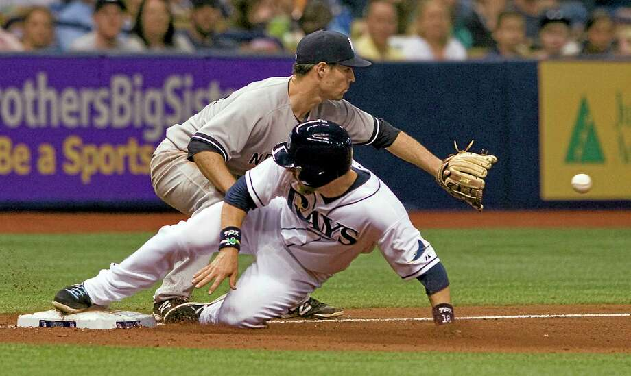 The Rays' Ben Zobrist, bottom, beats the throw to New York Yankees third baseman Scott Sizemore on a single by pinch-hitter Desmond Jennings in Friday's game. Photo: Steve Nesius  — The Associated Press   / FR69810 AP