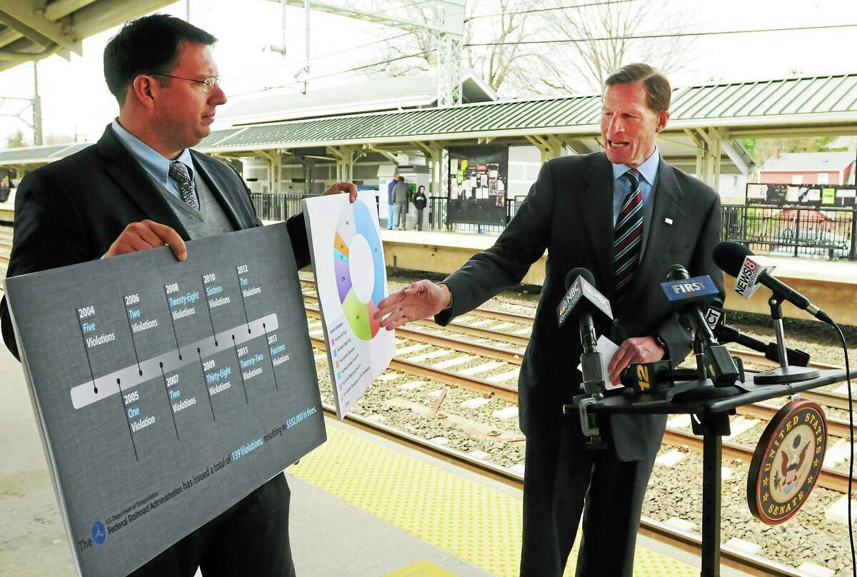 Milford Mayor Ben Blake, left, holds visual aids as U.S. Sen. Richard Blumenthal, D-Conn., holds a press conference at the Milford train station Friday about Metro-North safety fines.