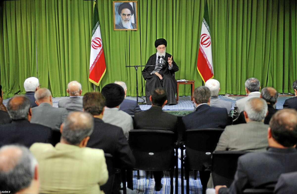 """In this picture released by an official website of the office of the Iranian supreme leader, Supreme Leader Ayatollah Ali Khamenei, speaks to a group of officials and scientists of the Atomic Energy Organization of Iran in Tehran, Iran, Wednesday, April 9, 2014. Iran's Supreme Leader urged Iran's negotiators Wednesday not to give in to """"coercive words"""" from world powers at talks over Tehran's nuclear program. Iran is celebrating its National Nuclear Technology Day as talks with world powers over its contested program continue in Vienna. A Portrait of the late revolutionary founder Ayatollah Khomeini hangs in background.(AP Photo/Office of the Iranian Supreme Leader)"""
