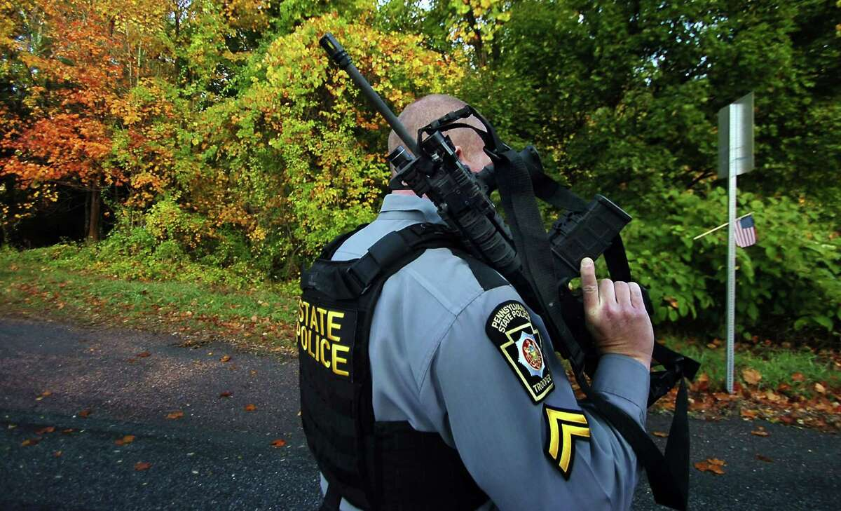 A Pennsylvania State Trooper walks with his rifle near a wooded area Wednesday, Oct. 8, 2014, in Price Township near Canadensis, Pa., searching for killer Eric Frein. A massive manhunt has been underway for 31-year-old Frein in the rugged terrain of the Pocono Mountains since Sept. 12. The self-taught survivalist is charged with killing Cpl. Bryon Dickson and seriously wounding Trooper Alex Douglass outside their barracks in Blooming Grove. (AP Photo/Scranton Times & Tribune, Butch Comegys) WILKES BARRE TIMES-LEADER OUT; MANDATORY CREDIT
