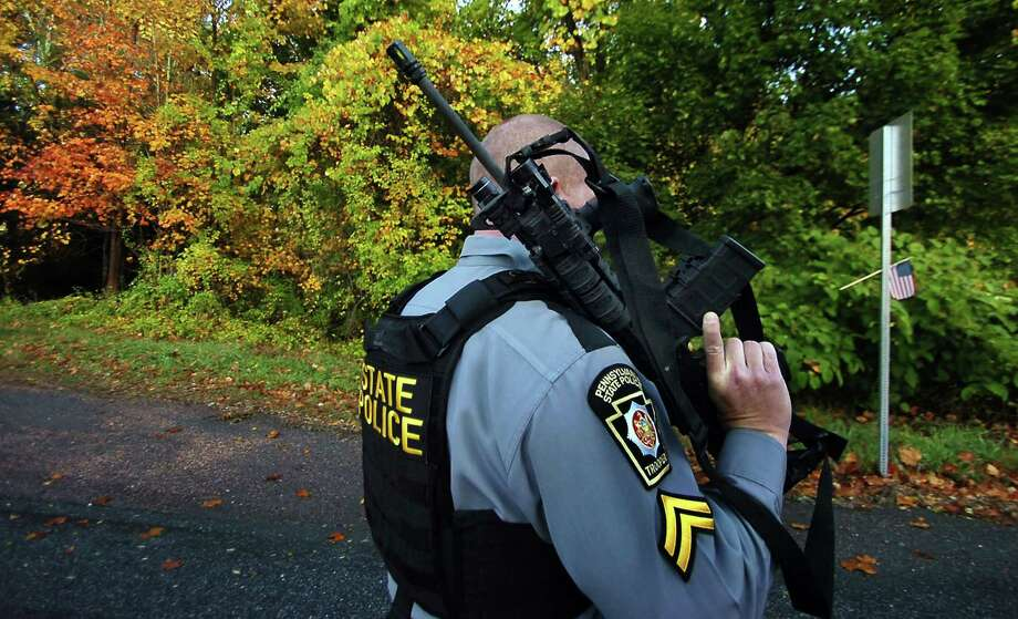A Pennsylvania State Trooper walks with his rifle near a wooded area Wednesday, Oct. 8, 2014, in Price Township near Canadensis, Pa., searching for killer Eric Frein. A massive manhunt has been underway for 31-year-old Frein in the rugged terrain of the Pocono Mountains since Sept. 12. The self-taught survivalist is charged with killing Cpl. Bryon Dickson and seriously wounding Trooper Alex Douglass outside their barracks in Blooming Grove. (AP Photo/Scranton Times & Tribune, Butch Comegys)  WILKES BARRE TIMES-LEADER OUT; MANDATORY CREDIT Photo: AP / The Scranton Times & Tribune