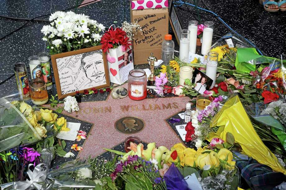 Flowers, photographs and candles surround the star of actor-comedian Robin Williams forming a makeshift memorial along the Hollywood Walk of Fame in Los Angeles on Tuesday, Aug. 12, 2014. Williams, 63, died at his San Francisco Bay Area home Monday in an apparent suicide. (AP Photo/Nick Ut) Photo: AP / AP
