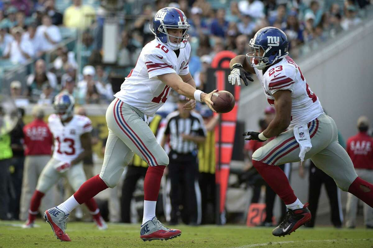 New York Giants quarterback Eli Manning hands the ball off to running back Rashad Jennings during a Nov. 30 game against the Jaguars in Jacksonville, Fla.