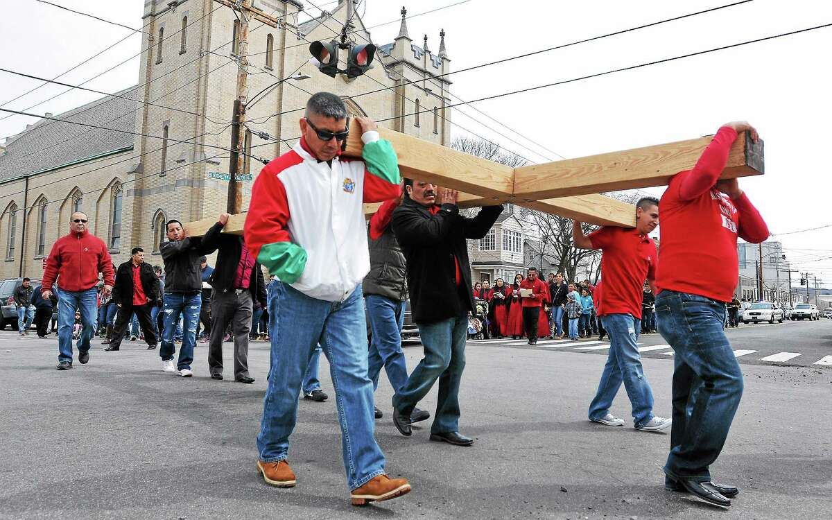 (Peter Casolino-New Haven Register) Congregants from the St. Rose of Lima Parish carry a large cross to celebrate the stations of the cross in Fair Haven on Good Friday. Hundreds from the predominately latino church carried two large crosses through the streets of Fair Haven, stopping to commemorate each station of the cross along the way. 4/18/14 pcasolino@newhavenregister.com