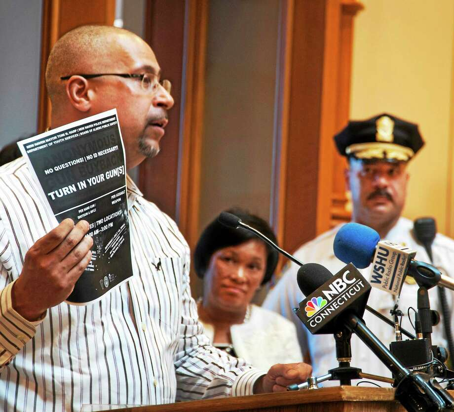 Jason Bartlett, left, New Haven youth services director, holds up a flier Monday promoting New Haven's summer gun buyback events. Looking on are Mayor Toni Harp, center, and Assistant Police Chief Luiz Casanova. Photo: Melanie Stengel — Register