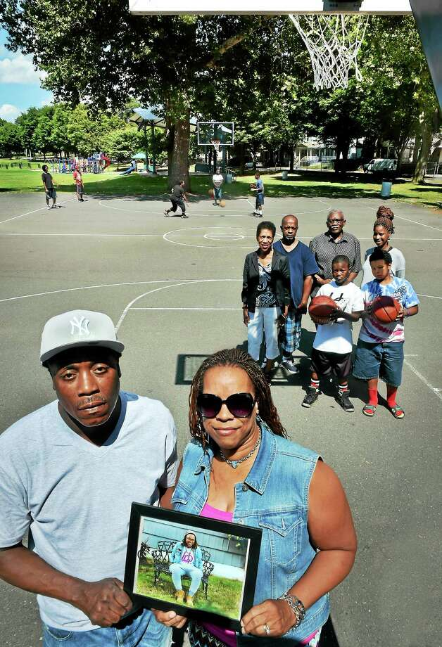 (Melanie Stengel - Register)  Greg (L) and Celest Fulcher hold a photo of  shooting victim, Erika Robinson, as they stand with family at the Goeffe Street basketball courts 8/14.  The family is holding a stop the violence basketball tournament in memory of Robinson. Photo: Journal Register Co.