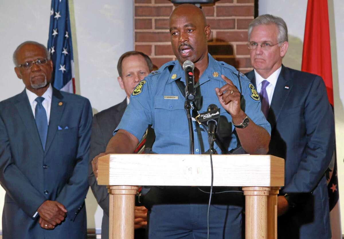 Capt. Ronald Johnson, foreground, commander of Missouri Highway Patrol's Troop C, addresses media at the University of Missouri St. Louis on Thursday, Aug. 14, 2014, at after Missouri Gov. Jay Nixon, right, announced that Johnson and the Highway Patrol will be taking over security at the Ferguson protest scene. St. Louis County Executive Charlie Dooley, left, and St. Louis Mayor Francis Slay also made statements. (AP Photo/St. Louis Post-Dispatch, Christian Gooden)