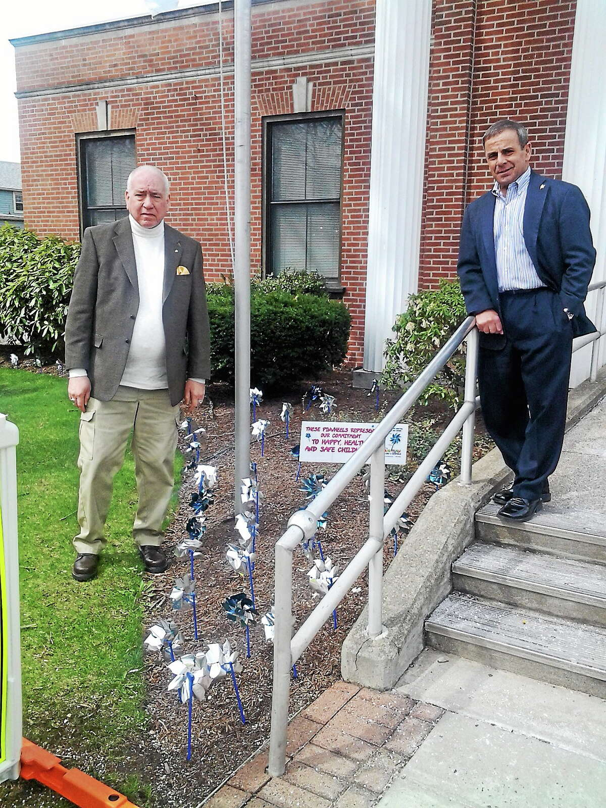 Ray Fowler, left, and First Selectman Michael Freda stand outside Town Hall with pinwheels symbolizing National Child Abuse Awareness Month.