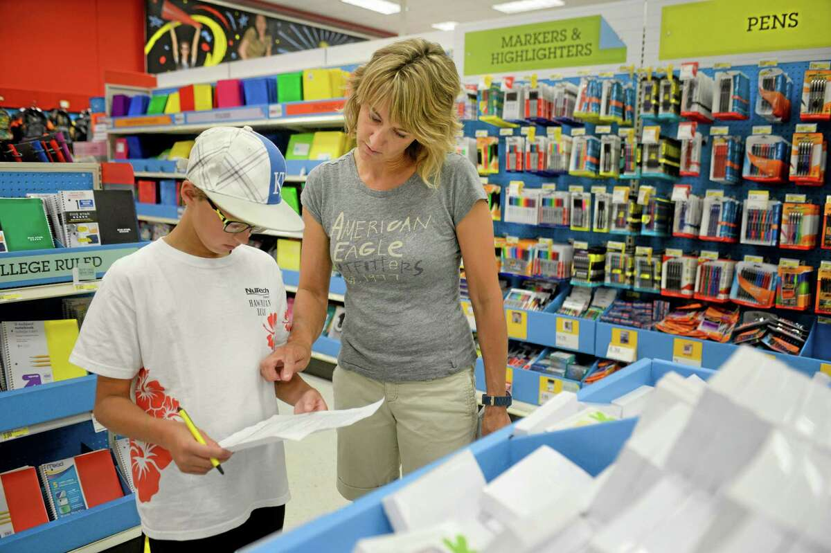 In this July 30 photo, Jill Courtney, right, shops for school supplies for her sons, Will, left, and Reid, not seen, at a Target store in St. Joseph, Missouri.