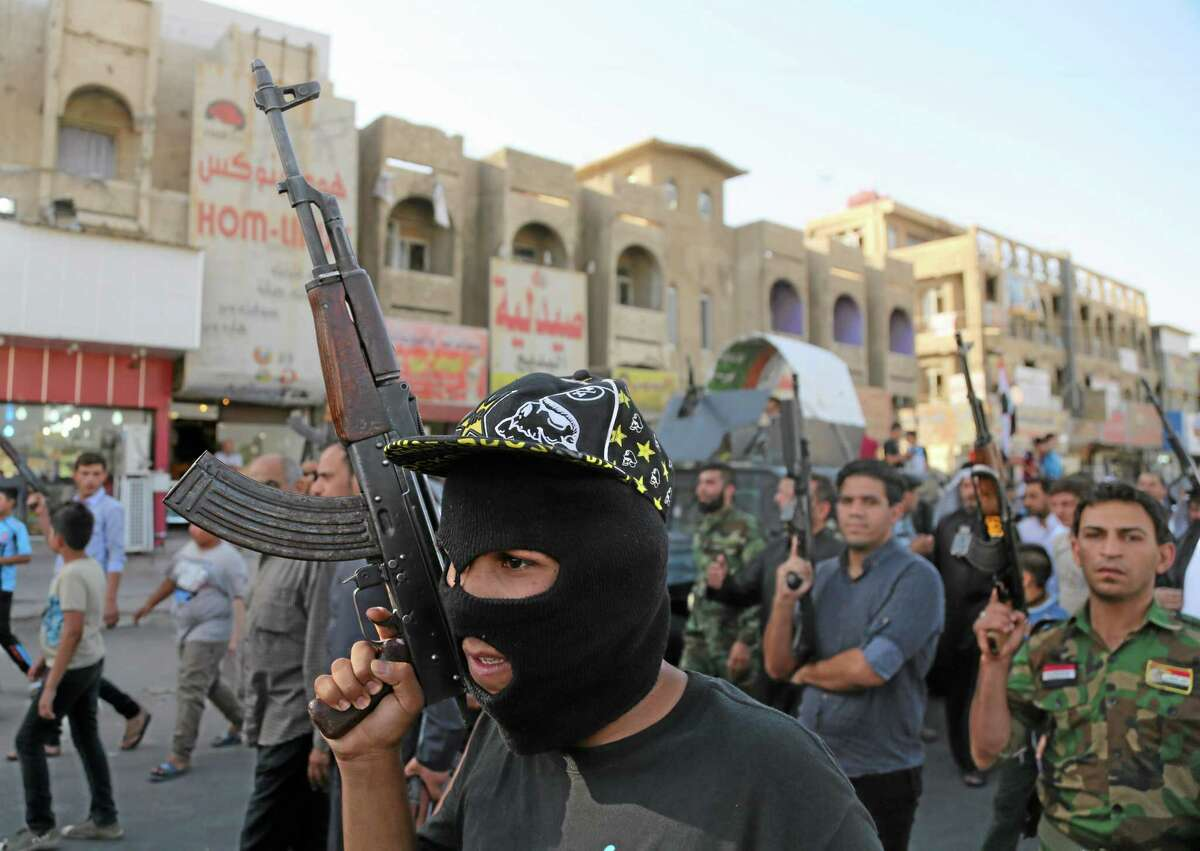 Shiite tribal fighters raise their weapons and chant slogans against the al-Qaida-inspired Islamic State of Iraq and the Levant (ISIL) in the northwest Baghdad's Shula neighborhood in Iraq Monday.