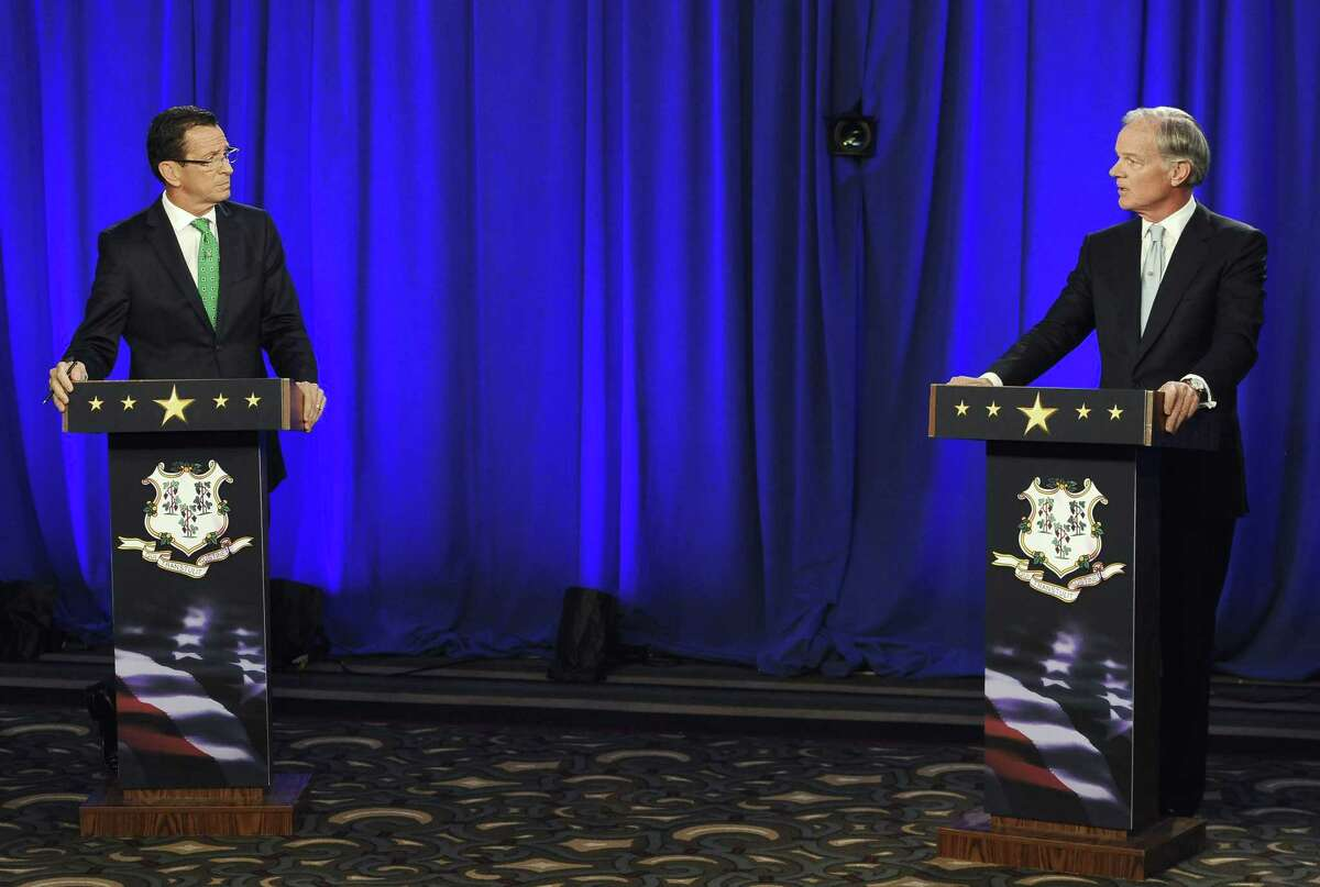 Gov. Dannel P. Malloy, left, and Republican candidate for governor Tom Foley look at one another during an exchange about gun laws during a debate Thursday in Hartford.