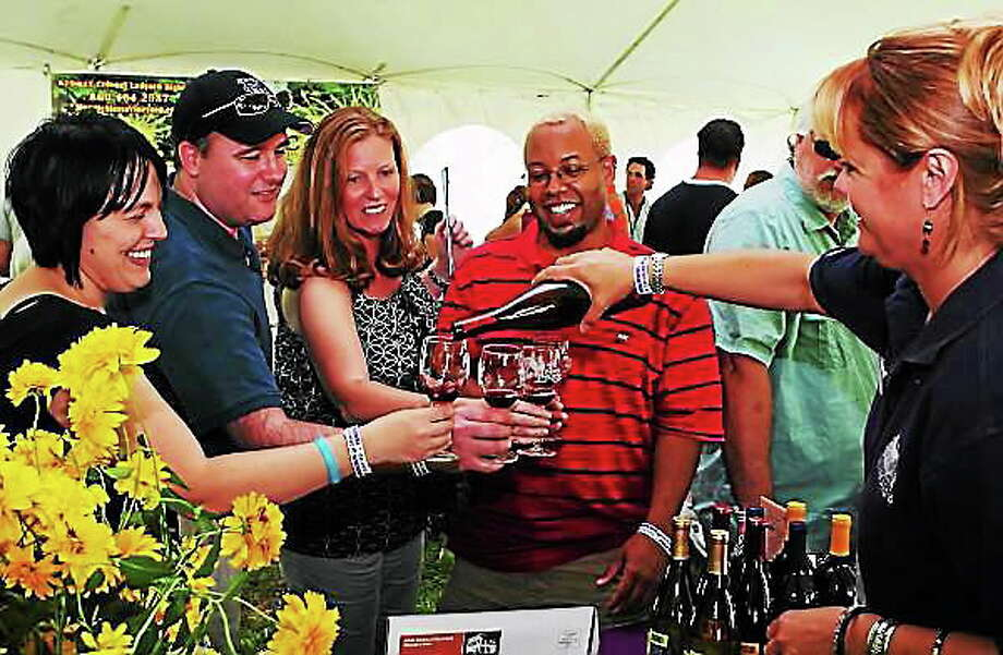 Visitors to a previous edition of the Shoreline Wine Festival in Guilford enjoy a taste of Connecticut wine. Photo: Contributed