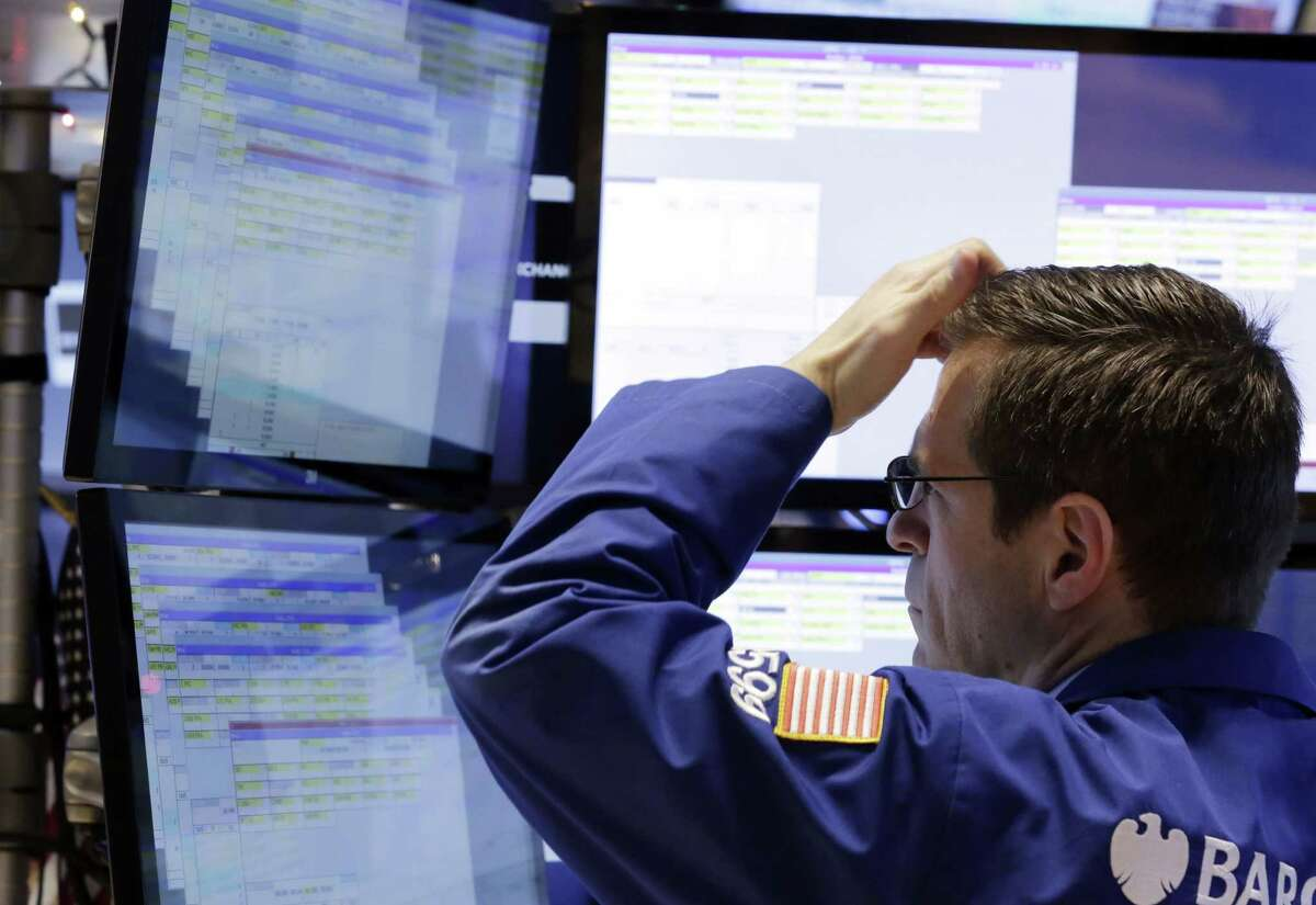 Specialist Charles Solomon works at his post on the floor of the New York Stock Exchange Friday.