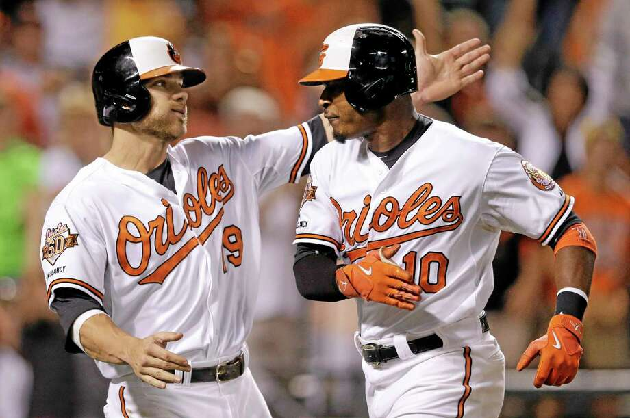 The Orioles' Chris Davis, left, greets teammate Adam Jones at home plate after he and Nick Markakis scored on Jones' home run in the eighth inning of Wednesday's 5-3 win over the Yankees. Photo: Patrick Semansky  — The Associated Press   / AP