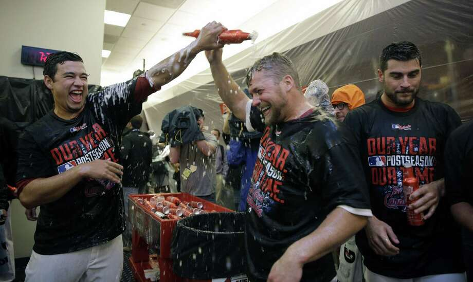St. Louis Cardinals players celebrate in the locker room after their 3-2 win over the Los Angeles Dodgers in Game 4 of baseball's NL Division Series, Tuesday, Oct. 7, 2014, in St. Louis. (AP Photo/Jeff Roberson) Photo: AP / AP