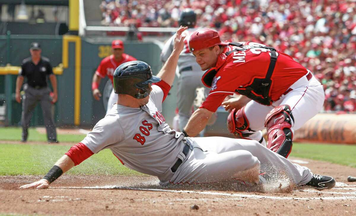 The Red Sox' Daniel Nava, left, scores in Wednesday's 5-4 win over the Reds.
