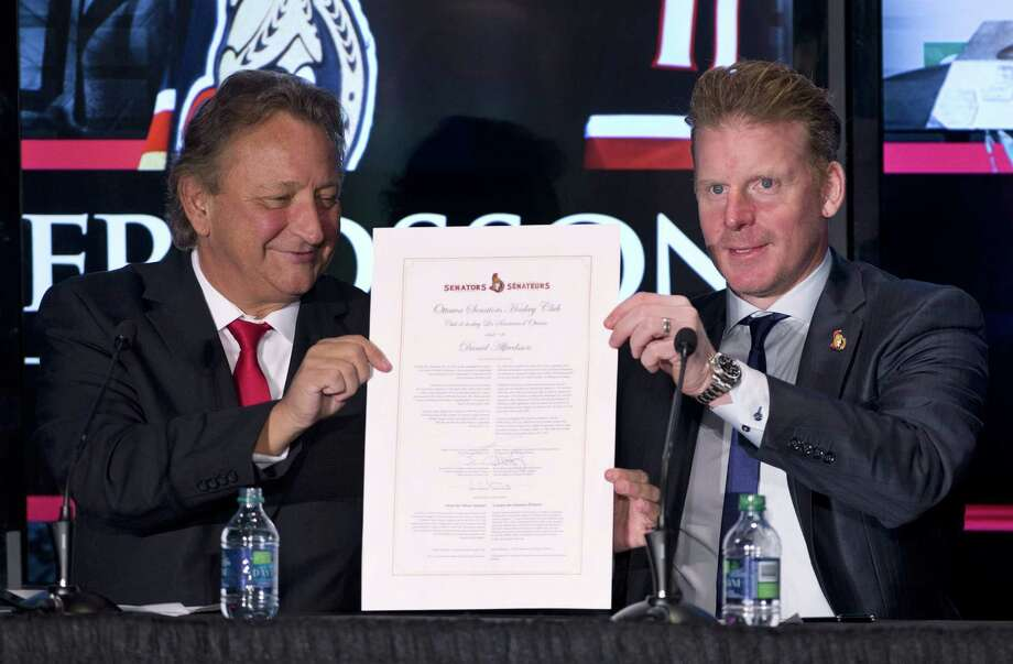 Ottawa Senators owner Eugene Melnyk, left, and Daniel Alfredsson hold up a one-day contract at a news conference announcing Alfredsson's retirement on Thursday in Ottawa. Photo: Adrian Wyld — The Canadian Press   / CP