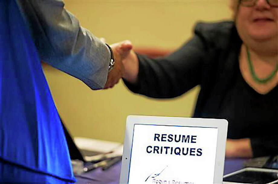 In this May 2013 file photo, a job seeker stops at a table offering resume critiques during a job fair held in Atlanta. Photo: The Associated Press   / FR69715 AP