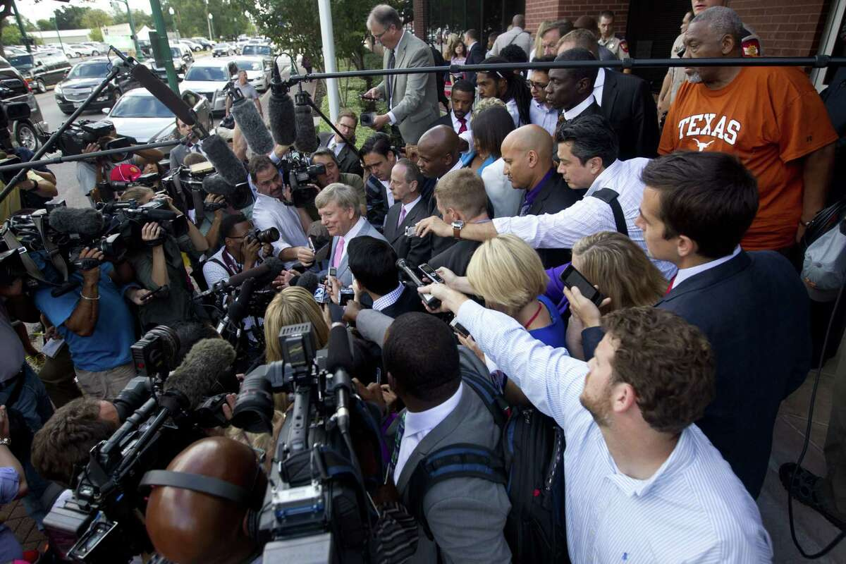 Houston attorney Rusty Hardin, center, speaks to the media after Minnesota Vikings running back Adrian Peterson appeared in court Wednesday in Conroe, Texas.