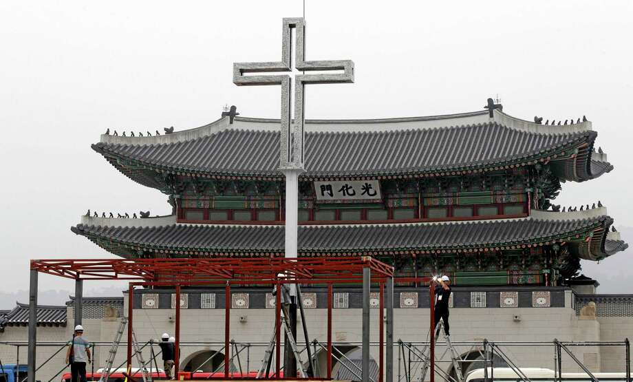 Workers set up a platform in prepare for a special holy mass by Pope Francis in front of the Gwanghwamun, the main gate of the 14th-century Gyeongbok Palace, in Seoul, South Korea, Wednesday, Aug. 13, 2014. Pope Francis is scheduled to make a five-day trip to South Korea, starting Aug. 14 to participate in a Catholic youth festival and to preside over a beatification ceremony for 124 Korean martyrs. (AP Photo/Lee Jin-man) Photo: AP / AP