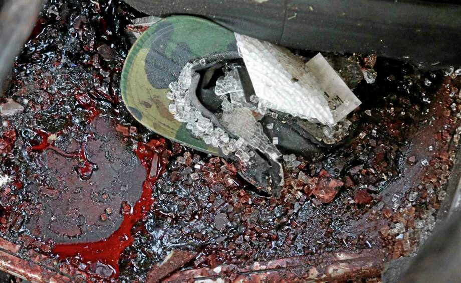 Blood covered pieces of glass and a military cap lie in the bus at a security post on the outskirts of Donetsk, eastern Ukraine, Wednesday, Aug. 13, 2014, where at least 12 militiamen fighting alongside government troops against pro-Russian rebels in eastern Ukraine have been killed in an ambush, a spokesman for their radical nationalist movement said Wednesday. (AP Photo/Sergei Grits) Photo: AP / AP