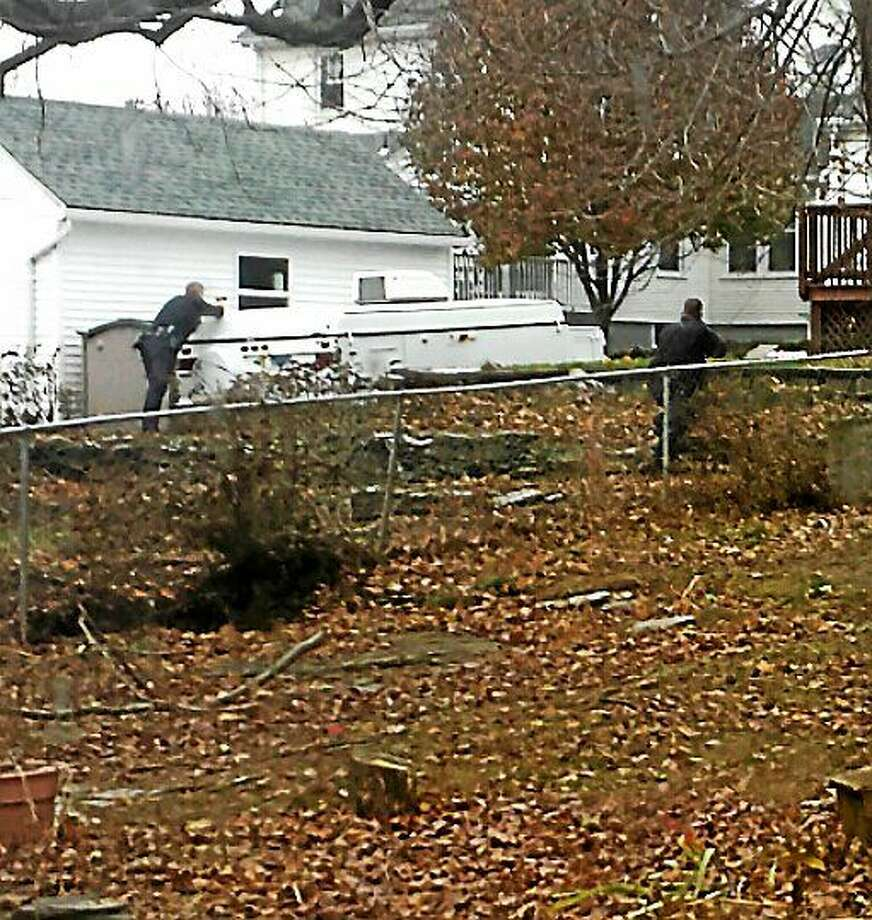 West Haven officers, with at least one gun drawn, approach a house before a man led them on a chase Tuesday afternoon. Police have identified the man as Stephen Turtzo, who is a retired city police officer. Photo: Contributed Photo