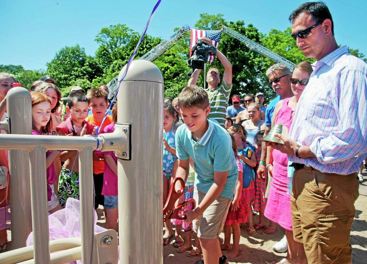Children crowd around Guy Bacon, brother of Sandy Hook shooting victim, Charlotte Bacon, as he cuts the ribbon to the West Haven playground built in Charlotte's memory. To the right are parents Joanne and Joel Bacon.