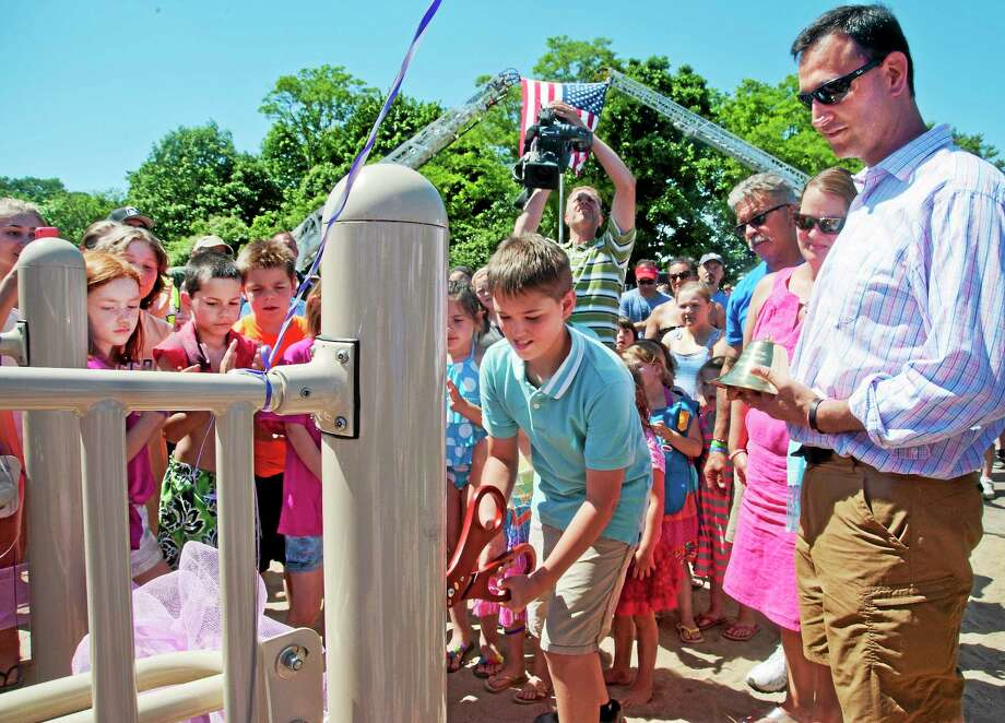Children crowd around Guy Bacon, brother of Sandy Hook shooting victim, Charlotte Bacon, as he cuts the ribbon to the West Haven playground built in Charlotte's memory. To the right are parents Joanne and Joel Bacon. Photo: (Melanie Stengel - New Haven Register)